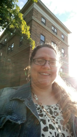 photo of jenni in front of a building with the sun behind her