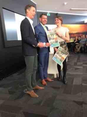 Jeroen Beelen en Angela Enthoven overhandigen de Bezoek Westland krant aan burgemeester Bouke Arends — bij Rabobank westland.