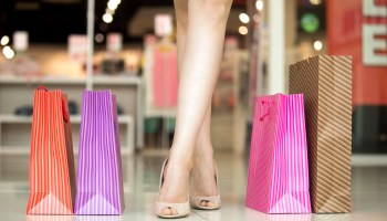 Close-up of woman's legs standing in shopping centre with bags