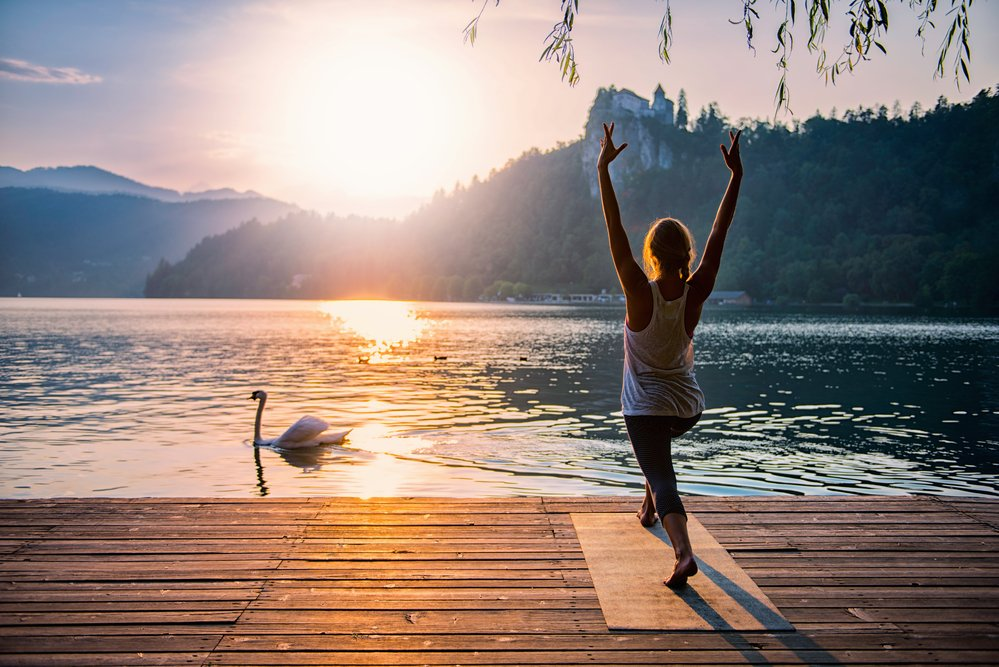 woman practicing Yoga by the lake