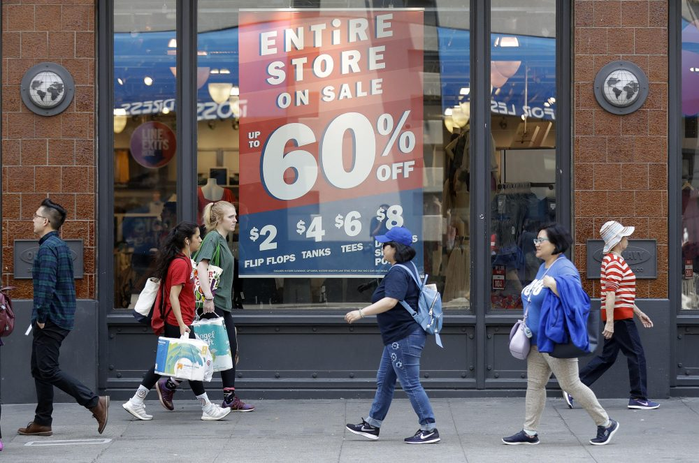In This July 3, 2018, Photo, Shoppers Walk Past Sale Signs In San Francisco