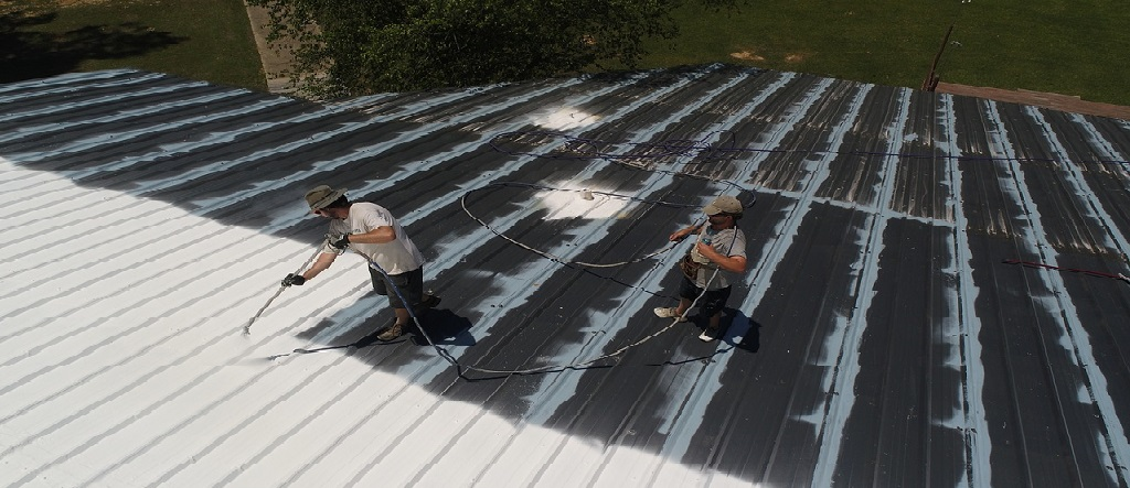 two guys applying roof coat