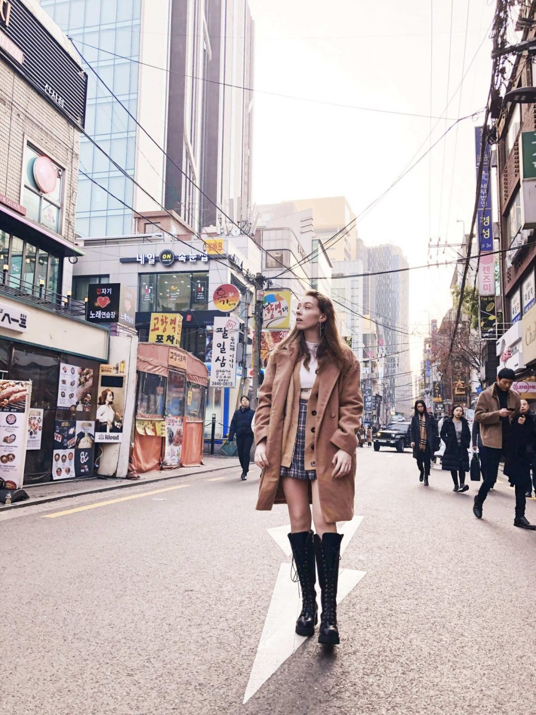 An image of Fii standing in the middle of a road with tall buildings and people either side. She is wearing a knee length brown coat with the buttons undone, so that you can see some of the clothes she wears underneath: a check pattern skirt and a brown cardigan. She is also wearing knee high black lace up boots, and is looking off to one side so you can see the long earrings.