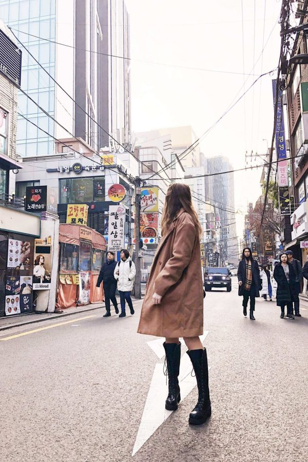 image of fii standing in the middle of a road looking backwards, wearing a knee-length camel coat, knee high black boots. There are tall buildings either side with Korean signs on them