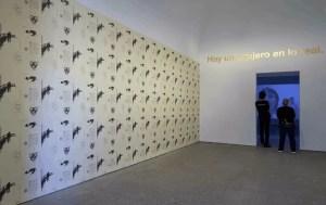 """Vista de una sala de la exposición Segunda vez de Dora García. Junto al muro empapelado con el lacaniano papel pintado se sitúa una obra de la serie Golden Sentences. Al fondo, la película """"La lección respiratoria""""."""