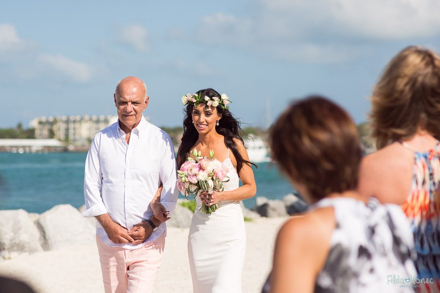 father walks his daughter to the ceremony on the beach at sunset key florida