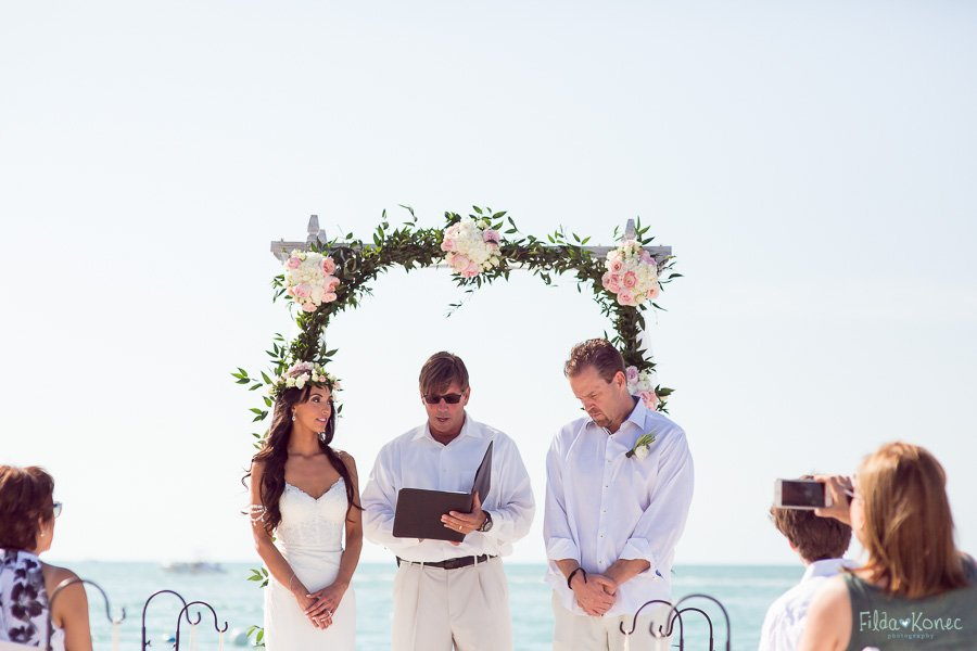 couple listens to the officiant during their beach ceremony on sunset key florida