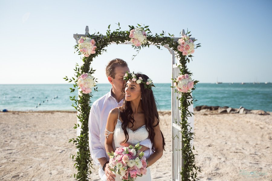 intimate photo of couple standing near the arch at sunset key florida