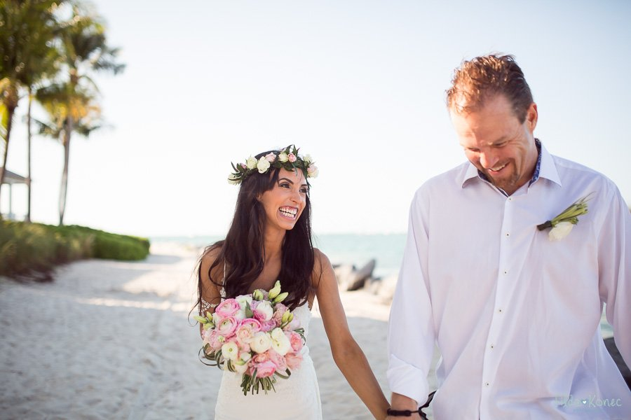 happy wedding couple walks on the sand at sunset key