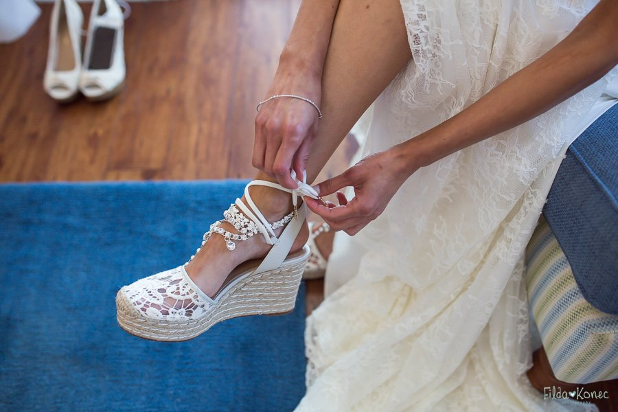 bride is putting her shoes on before the ceremony
