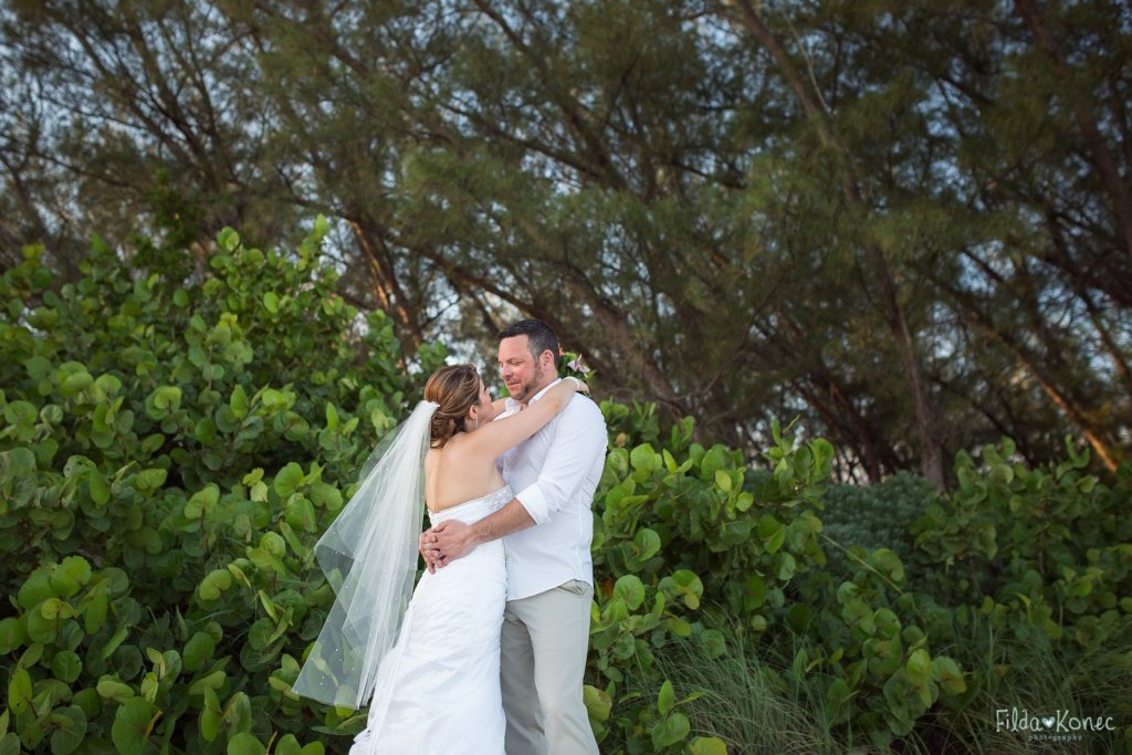 bride and groom hug with beautiful florida foliage in the background