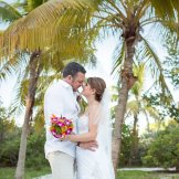 wedding couple kisses with florida palm trees in the background