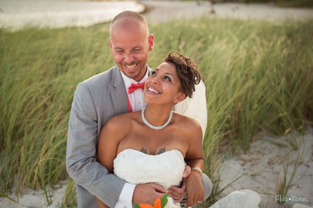 Bride and groom sitting in the grass and laughing