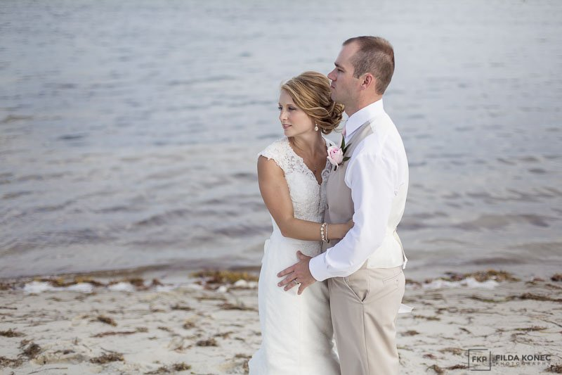 bride and groom standing near the ocean