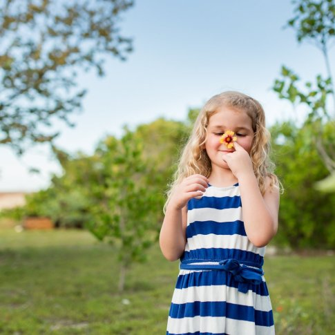 little girl plays with flower on family session in key west