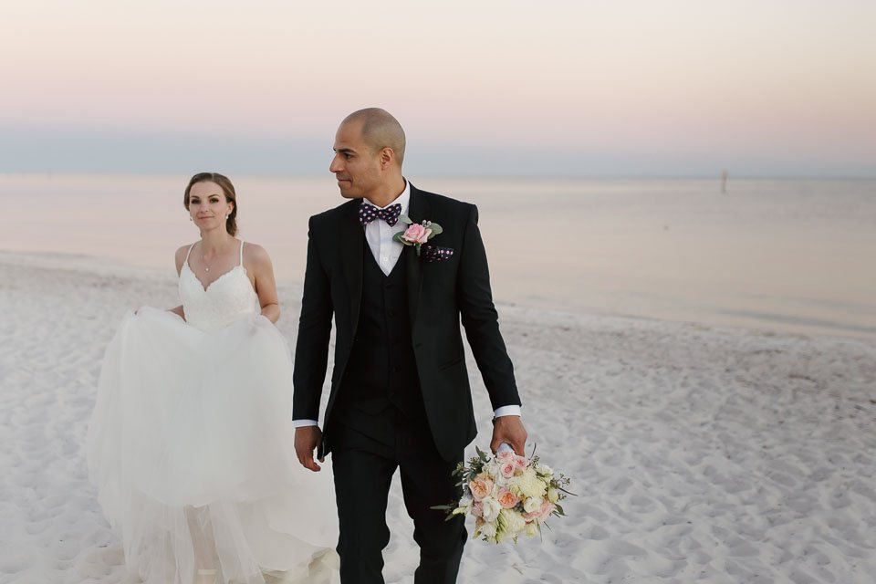 bride and groom walk down smathers beach on their wedding day