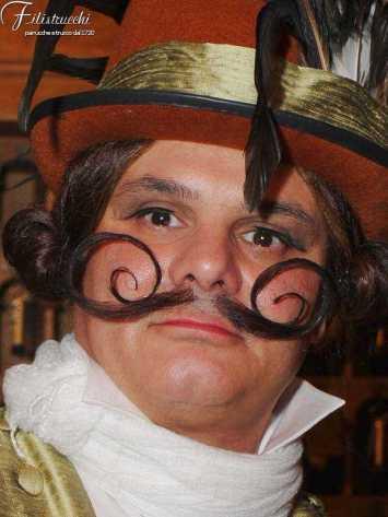 Immagine di attore paffuto con cappello ed abbigliamento di scena che indossa vistosi baffi arricciati posticci