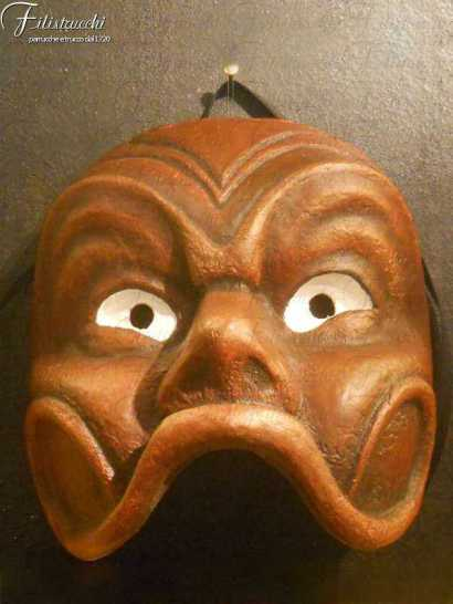 immagine che descrive una Maschera da Arlecchino arancione con occhi bianchi appesa ad un chiodo