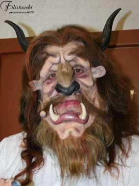 Uomo che indossa una maschera con denti e corna la bestia della favola: la bella e la bestia.