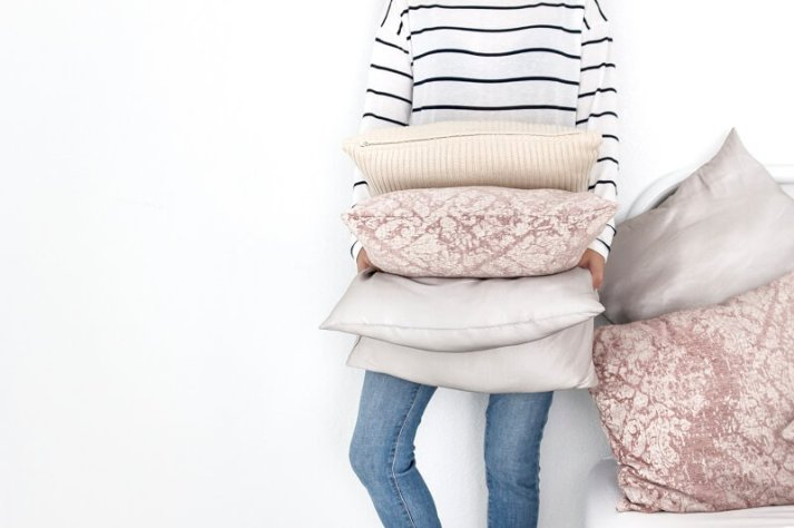 woman in striped sweater and jeans against white background getting ready to declutter extra pillows