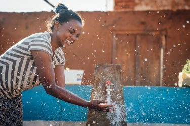 Tahina splashes in clean water from the water point next to her house, in the village of Ambatoantrano, Bongolava, Madagascar, September 2017.