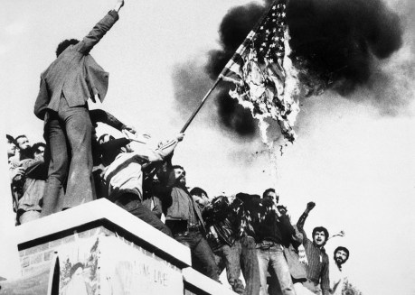 11/9/1979 Teheran, Iran: Demonstrators perched atop of the United States Embassy wall, burn an American flag, the fourth American flag to be burned since the students seized the embassy and more than 60 hostages Nov. 4th.