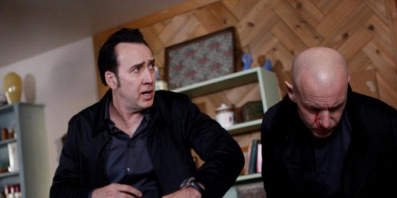 2017 Nicolas Cage Humanity Bureau - Nicolas Cage stands in a living room with a bald man.