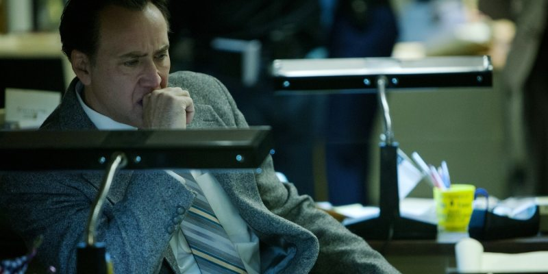 2017 Nicolas Cage sitting at a desk wearing a grey blazer biting his knuckle looking extremely concerned about something only Nicolas Cage could ever be concerned about.