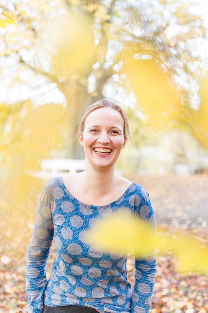 Frau im Herbst, lacht in Kamera