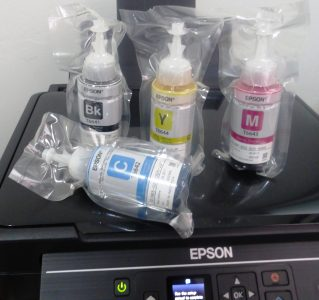 The printer is packaged with Cyan, Magenta, Yellow, and Black ink bottles that the user must carefully fill the tanks with.
