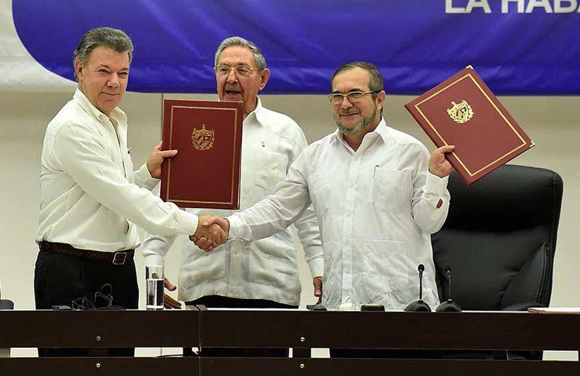 Colombian President Juan Manuel Santos celebrates the beginnings of peace with FARC commander Rodrigo Londoño Echeverri, aka, Timochenko. (Credit: Presidencia de la República / Juan David Tena. SIG)