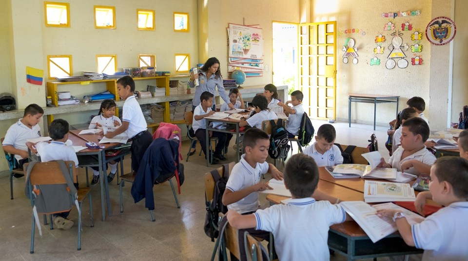 A typical Escuela Nueva classroom, featuring students within two grade levels sitting in group desks and actively discussing their lessons. (Credit: Jared Wade)
