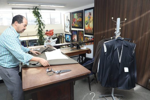 Maestro Danilo Vasco, the expert tailor, works his craft in his mezzanine, above the retail area. (photo credit: Loren Moss)