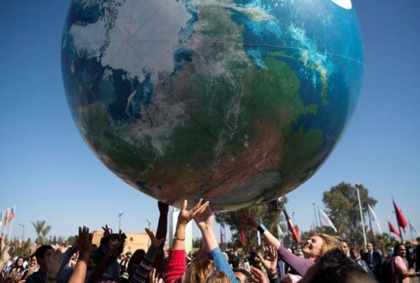 966361-des-membres-des-delegations-internationales-a-la-cop22-jouent-avec-un-globe-terrestre-geant-le-18-no