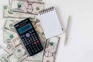 a calculator,notebook and notes of money