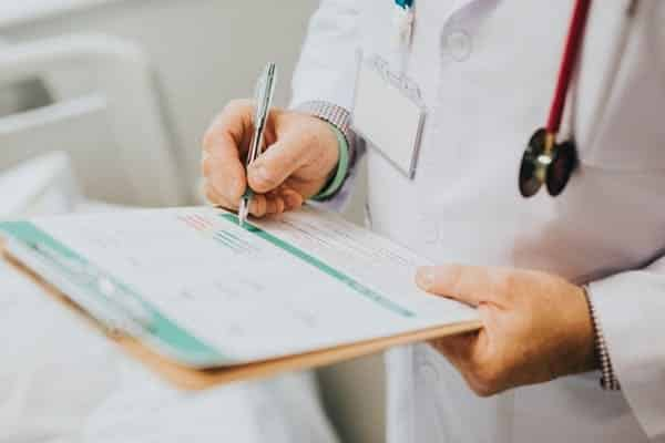 Doctor signing paper signifying the advantages of working for a large organization