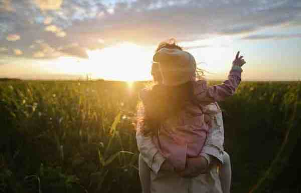 A family out in a field with the child pointing at the sky symbolizing the pursuit of financial independence with kids