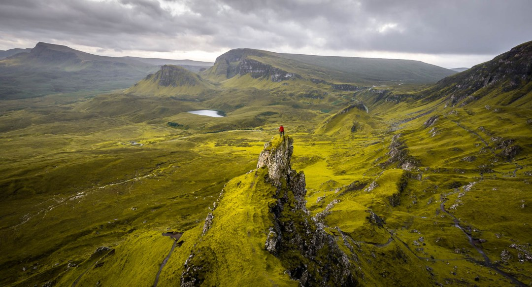 Ben Campbell standing on spire at Quiraing Isle of Skye..
