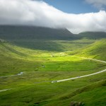 Faroese road through green valley.