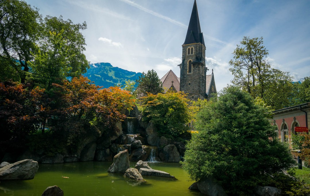 Colourful leaves and fountain pool with church spire in Interlaken.