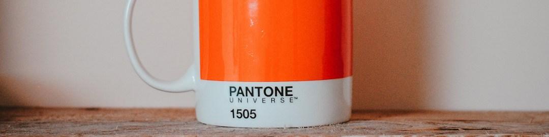 Taza color Pantone 1505 sobre estante de madera