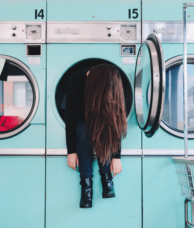 an image of a girl hanging out of a washing machine to represent the emotional turmoil following ADHD diagnosis