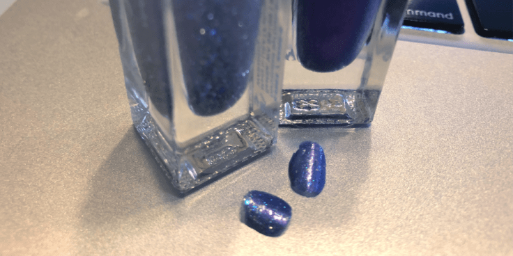 Image of sparkly purple fingernail polish from two fingernails that has popped off her fingernails while blogging.
