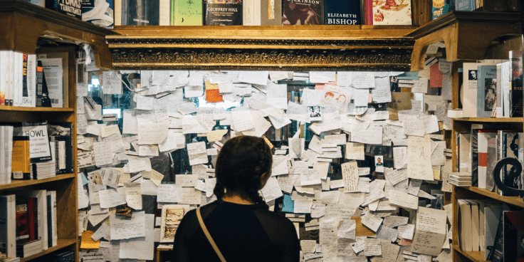 An image showing a young woman in pigtails (seen from behind) staring at a wall full of pinned notes and cards in the middle of shelves full of books. The image is meant as a metaphor for the ADHD brain being overwhelmed by ideas and information.