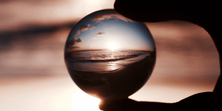 Silhouetted fingers holding a glass ball in front of a colorful sunset.