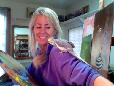 cockatiel bird on shoulder of artist