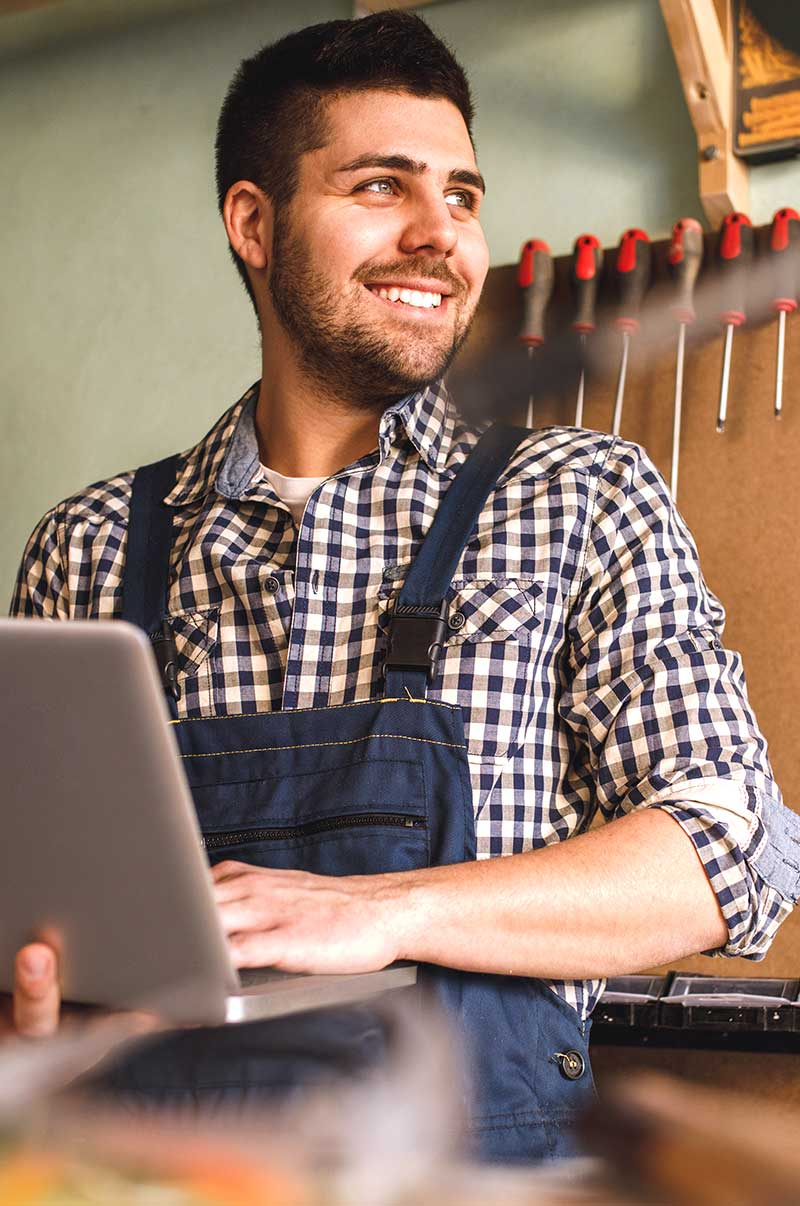 smiling woodworker with computer