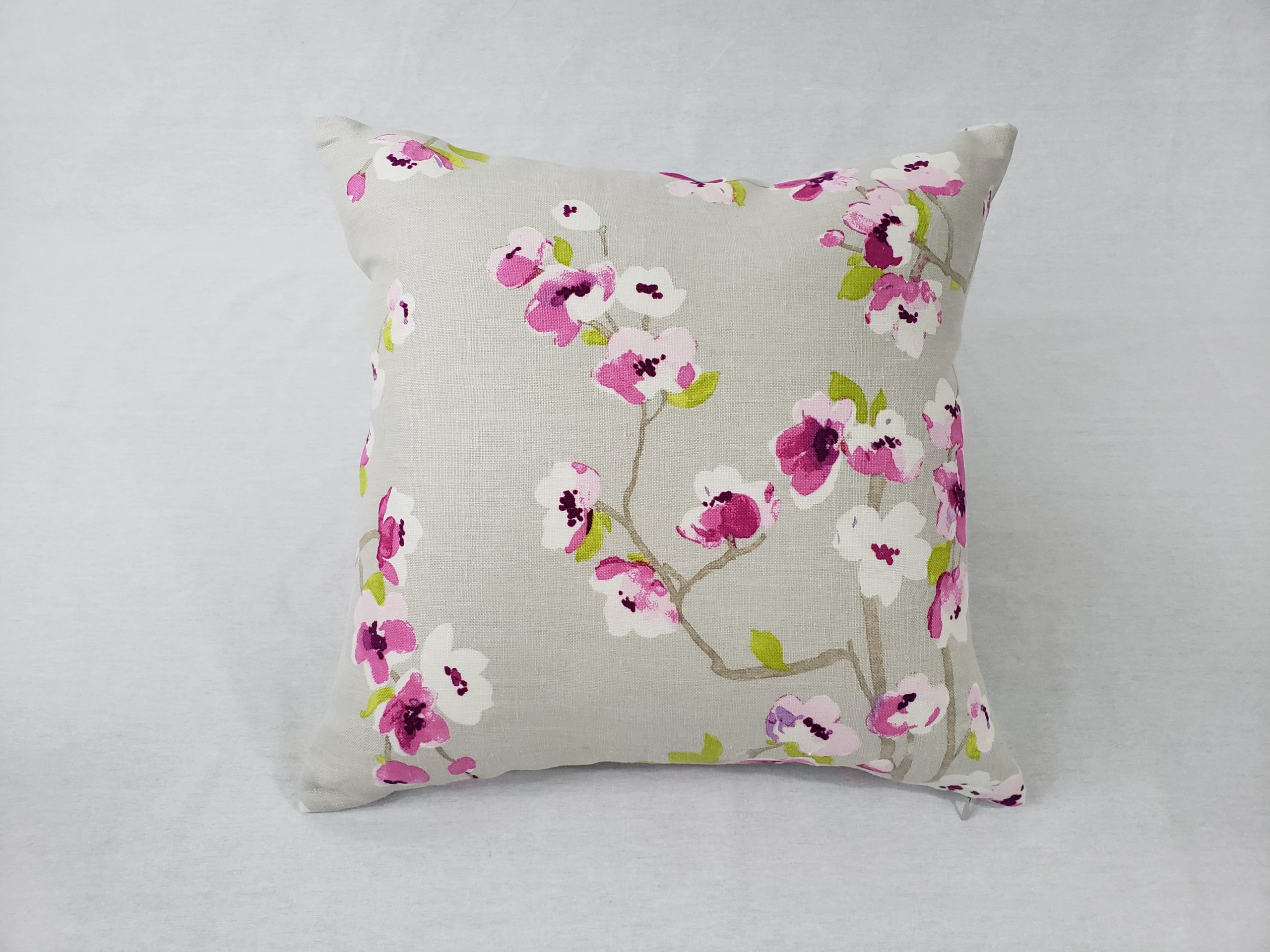 A pretty floral cushion with pink accents