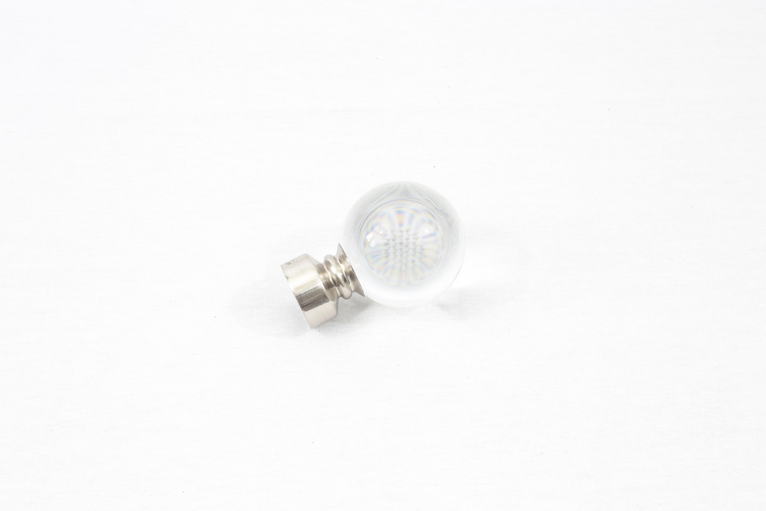 A brushed nickel glass ball finial for drapery rods