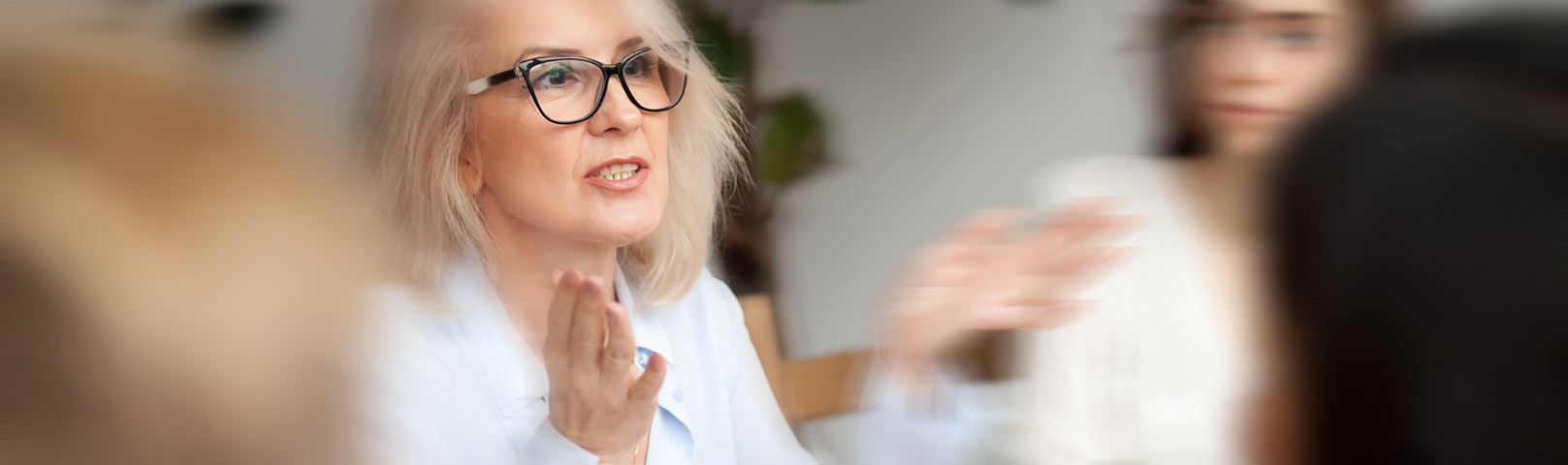 a mature woman speaks before a group in a room where everything around her appears blurry due to her tinnitus
